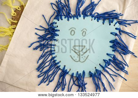 High Angle Still Life of Children Craft of Blue Lion Face with Tied Yarn Mane on Table Top with Copy Space