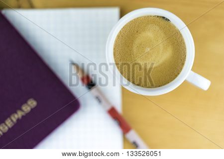 Travel Planning Concept Image - High Angle Still Life View of Frothy Cup of Coffee on Wood Desk with Pad of Paper Pencil and Passport in Diffuse Focus in Background
