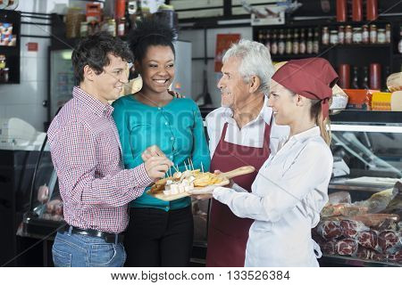 Salespeople Offering Cheese Samples To Customers In Shop