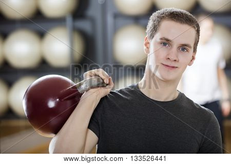 Attractive Man Exercising With Kettlebell In Gym