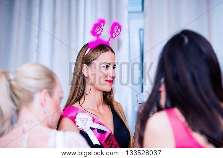 Cheerful bride and happy bridesmaids celebrating hen party with drinks. Women enjoying a bachelorette party.