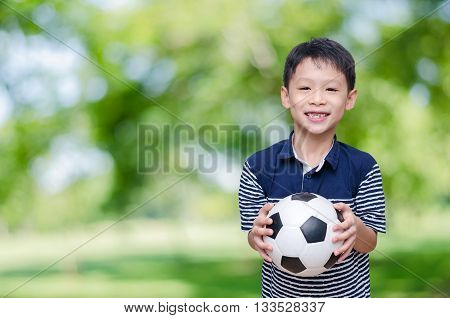 Young Asian boy holding soccor ball in park