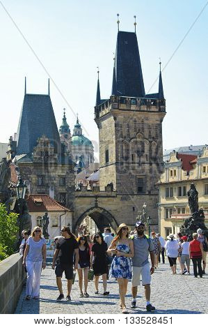 Prague Czech - 03 July 2015: Praguers and tourists entering the Charles Bridge through the arch of Lesser Town Tower.