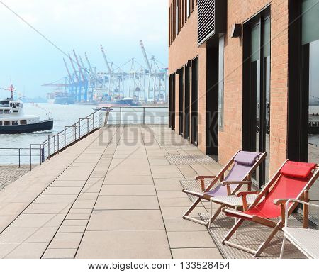 View to Hamburg harbor. Beach chairs in the foreground and container harbor in the background.