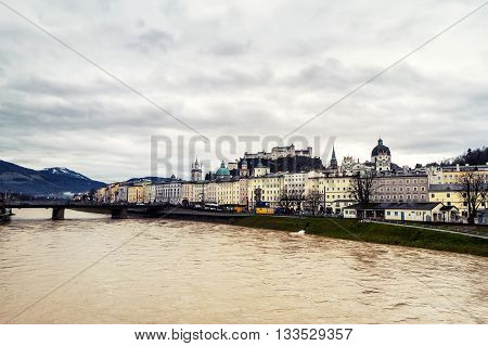 Aerial view of Salzburg, Austria with cloudy sky. Castle and Cathedral with mountain at the background