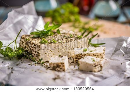 Artisan soft cheese with herbs crust, studio shot