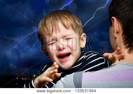 Crying boy in the hands of  father on the background of lightning