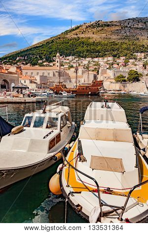 DUBROVNIK, CROATIA - JULY 19: Old port of Dubrovnik with cruise boats and old town in background. Many tourists gather here to enjoy boat cruises, on July 19, 2014 in Dubrovnik, Croatia.