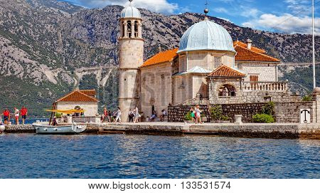 KOTOR, MONTENEGRO - JULY 19: Tourists in famous Church Our Lady of the Rocks. Our Lady of the Rocks is one of the two islets off the coast of Perast in Bay of Kotor, on July 19, 2014 in Kotor, Montenegro.