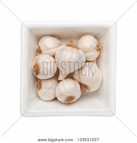 Cloves of garlic in a square bowl isolated on white background