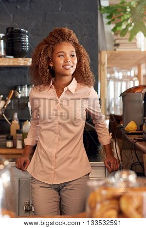 Attractive young woman standing behing the counter of a cafe