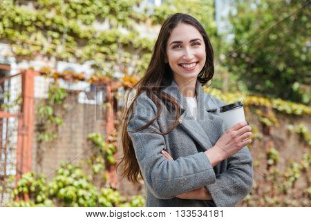 Smiling beauiful cheerful girl holding take away coffe cup outdoors
