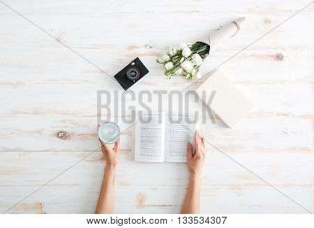 Women hands turn over book pages with glass of water, flowers and camera on the wooden desk