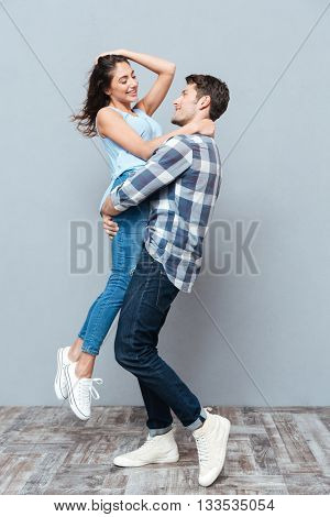 Handsome man picking up and hugging his girlfriend isolated on gray background