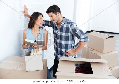 Young pretty happy married couple unpacking in new flat