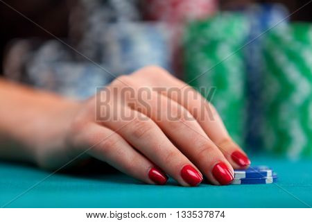 Woman betting gambling chips. Focus on hand. Close up
