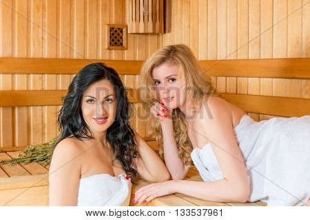Beautiful Girl And Young Relax In The Finnish Sauna