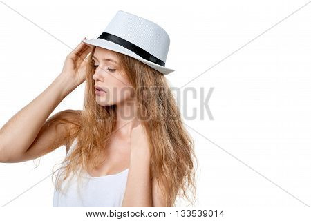 Closeup of beautiful slytish woman posing in fedora hat looking away over white background