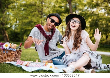 Cheerful young couple listening to music from smarphone and singing on picnic outdoors