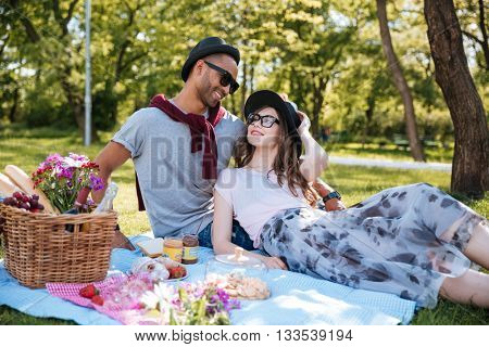 Cheerful young couple in love resting and having picnic in park