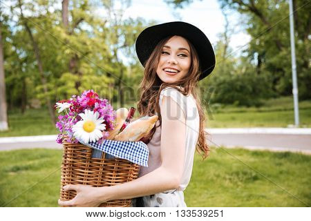 Smiling attractive young woman in hat holding basket with flowers, drinks and food