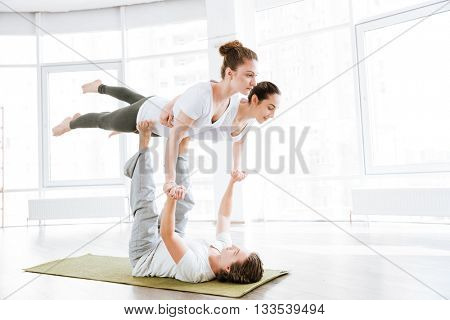 Group of two young women and man balancing and doing acro yoga in studio