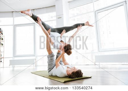 Beautiful couple doing flexibility workout in yoga studio together