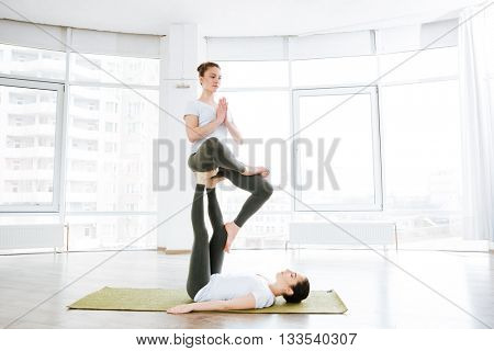 Two pretty young women practicing acro yoga on green mat in studio together