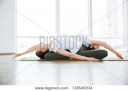 Two concentrated young women doing stretching exercises in yoga center