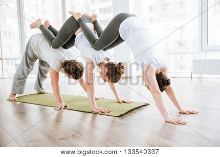 Man and two women practicing acro yoga exercises in group together