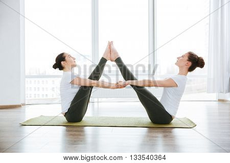 Two slim young women stretching legs on green yoga mat