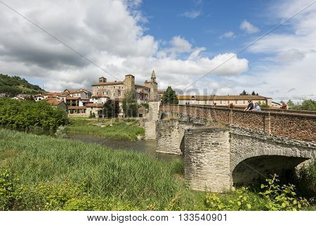Monastero Bormida Italy - May 29 2016: Bridge people river houses and Church of Monastero Bormida in Piedmont Italy