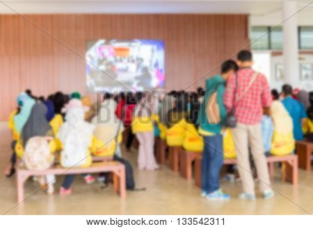 Blurred abstract background of university students sitting in a lecture room with Movie screen education high school technology and people concept: Blurry view from back of the classroom: