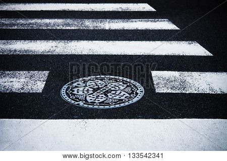 Japanese manhole with metal cover on street cross road. Black asphalt and white road marking line, Tokyo street, Japan.