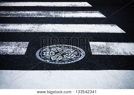 Japanese manhole with metal cover on street cross road. Black asphalt and white road marking line, Tokyo street, Japan.