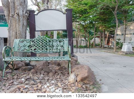metal Green chair in the garden. Under the tree and space for label add text above