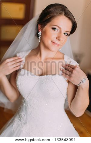 Close up portrait of beautiful caucasian mid adult bride showing her white dress.