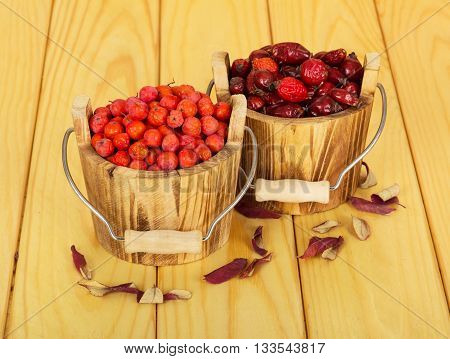 Rose hips and rowan berries in wooden buckets on a background of light wood.