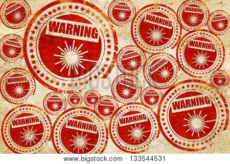 Laser warning sign, red stamp on a grunge paper texture