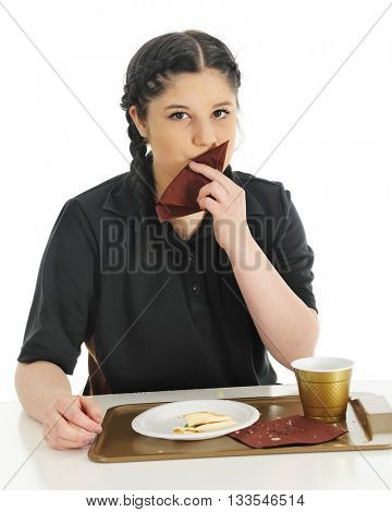An attractive teen girl wiping the crumbs from her lips after enjoying a fast food breakfast.  On a white background.