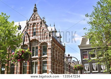 Canal at Amsterdam city, Netherlands. Old town houses of cobblestone with clear blue sky. Antique, traditional row houses in Amsterdam, the Netherlands.