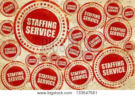 staffing service, red stamp on a grunge paper texture