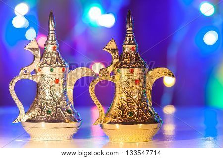 Gold and Silver Arabic Coffee pots in colorful illuminated background. Ramadan and Eid concept background