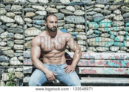 Handsome Muscular Shirtless Hunk Man Outdoor in City Setting, Sitting on Bench. Showing Healthy Body While Looking Away to a Side
