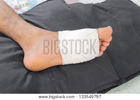 Gauze bandage the foottreating patients with foot ulcersmale is wrapping his Foot injury with bandage.( select focus Gauze bandage)