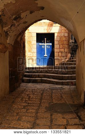 Arch passage in old Jaffa street leading to the church door with the cross. Israel.
