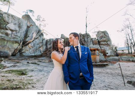 Young happy newlywed bride leaning on shoulder of her handsome confident new husband in blue suit. Magnificent mountain landscape as backround.