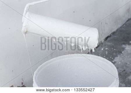 White paint dripping with paint roller on the edge paint bucket.(select focus front paint roller and soft-focus background)