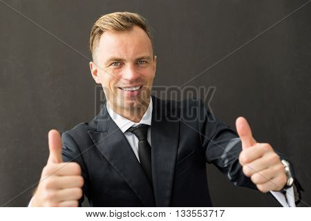 Happy business man showing both thumbs up