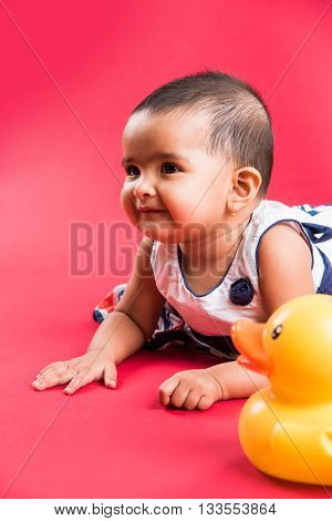 Indian toddler playing over colourful background, cute little indian baby girl playing with toys, indian baby girl playing, asian infant playing